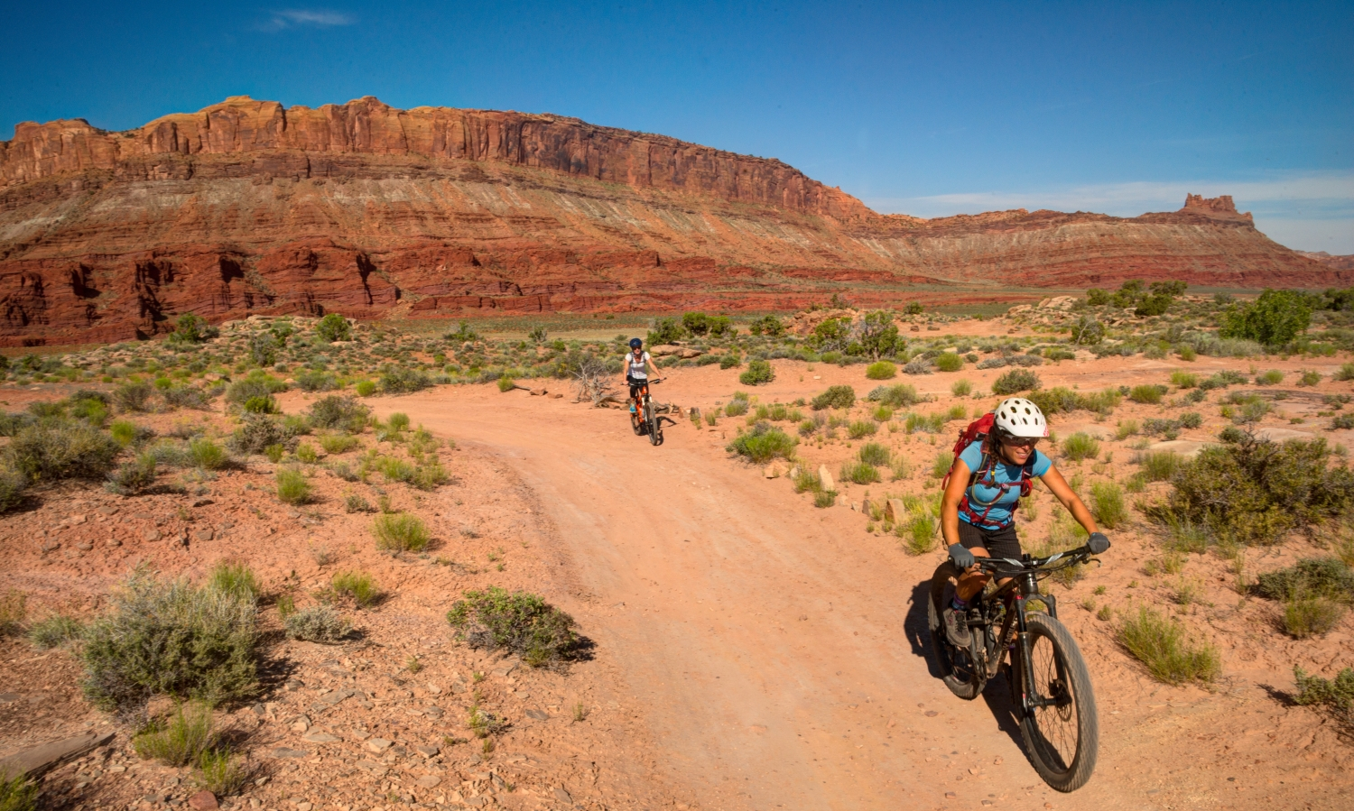 The numerous bands of the Cutler formation in the Moab Rim make for a colorful background to a flowy ride.