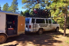 The Rim Tours mountain bike van with bikes on rack and trailer with gear