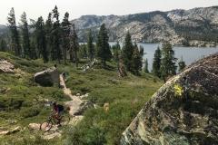 Mountain-Biker-Through-California-Sierra-Lake-Background