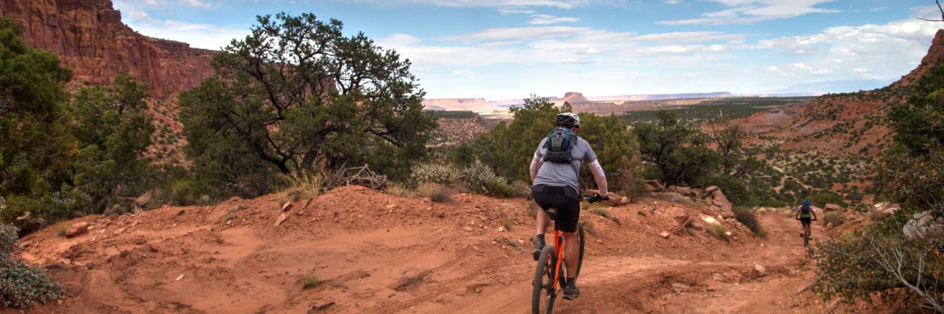 Mountain bikers descend The Flint Trail at the beginning of their guided mountain bike tour of The Maze in Canyonlands National Park
