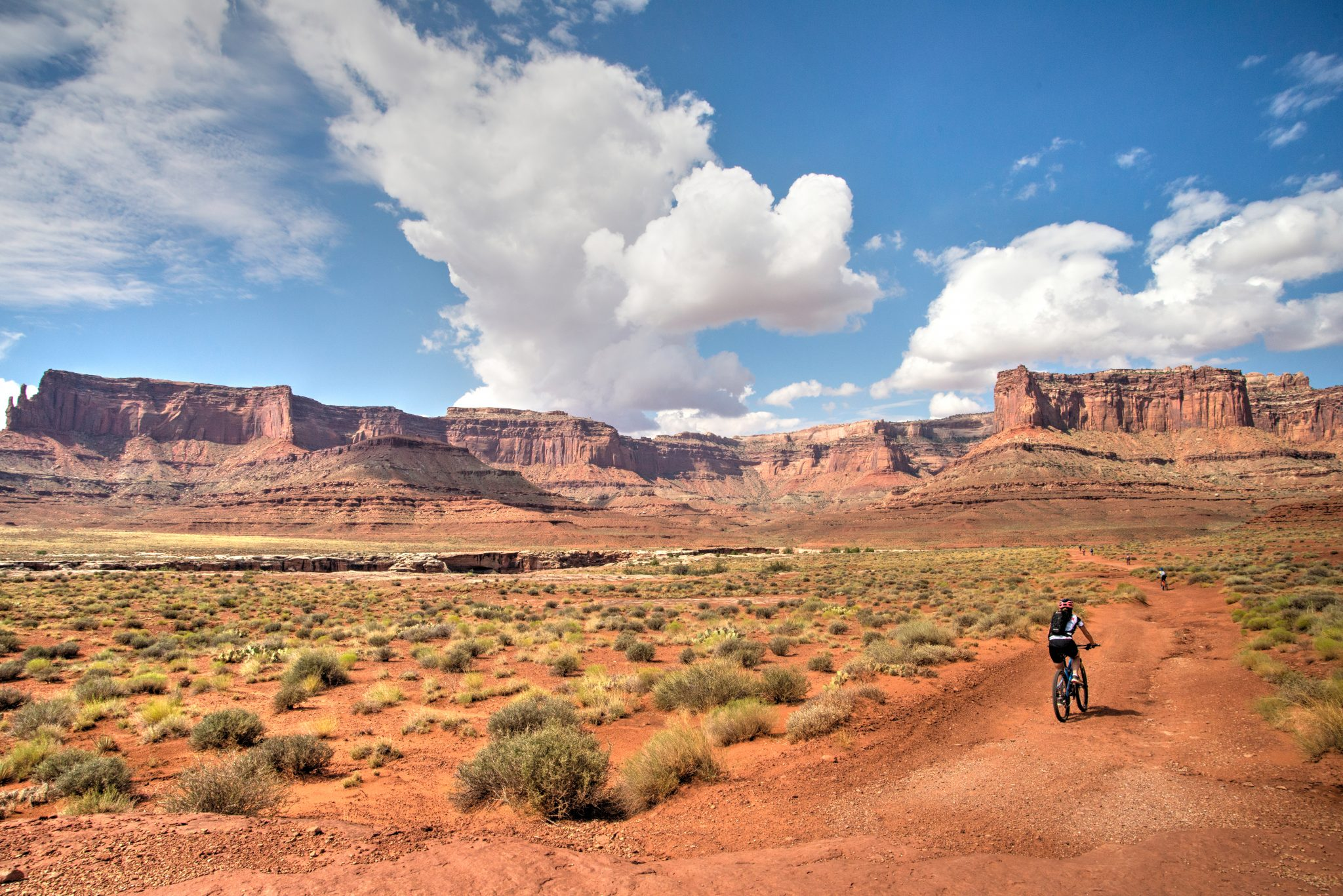 Riders string out on the White Rim Trail passing Musselman Arch on a 4-day guided mountain bike tour