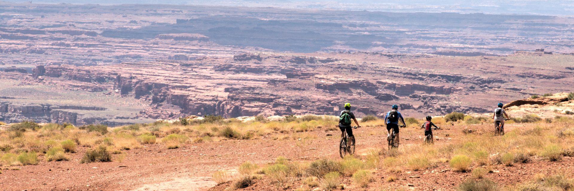 A family descends a slope heading toward Little Bridge Canyon on The White Rim Trail