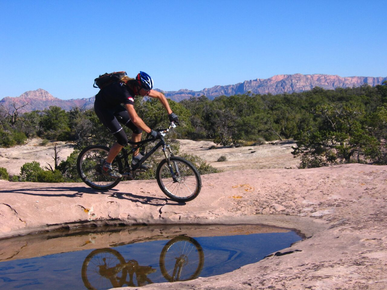 Riding the slickrock of Gooseberry Mesa, a mountain biker dream rounds a pothole filled from recent rains