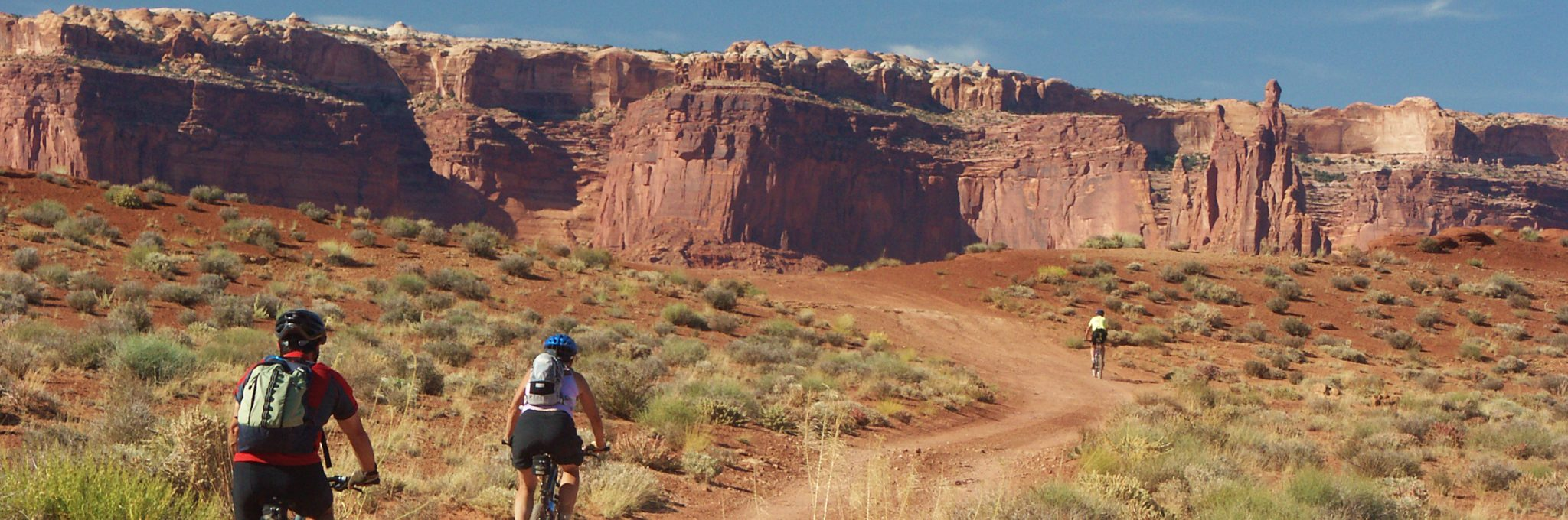 Bikers ride the White Rim Trail toward the Airport Towers campground in Island in the Sky District, Canyonlands NP