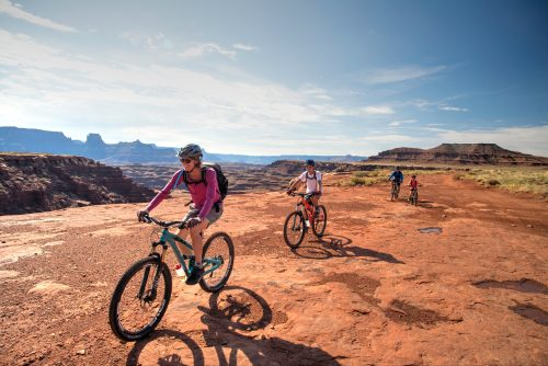 A family follows their guide along The White Rim Trail above Little Bridge Canyon in Canyonlands National Park, Island in the Sky District