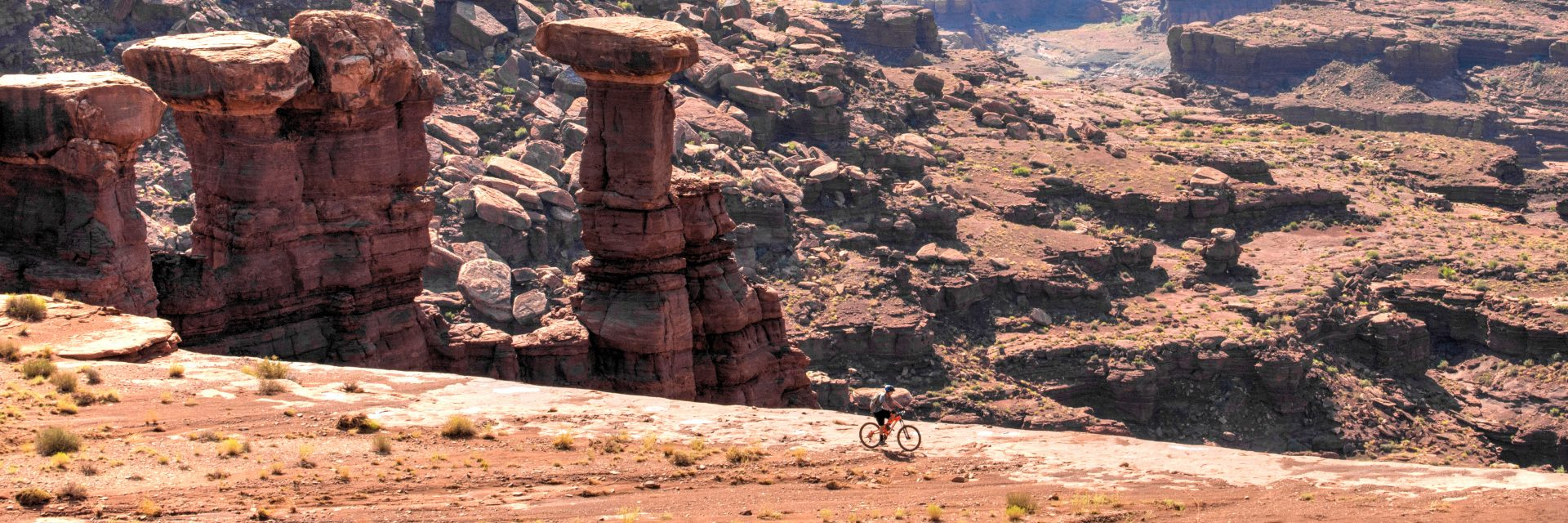 Lone rider skirts the edge of White Rim, Canyonlands NP, Moab UT