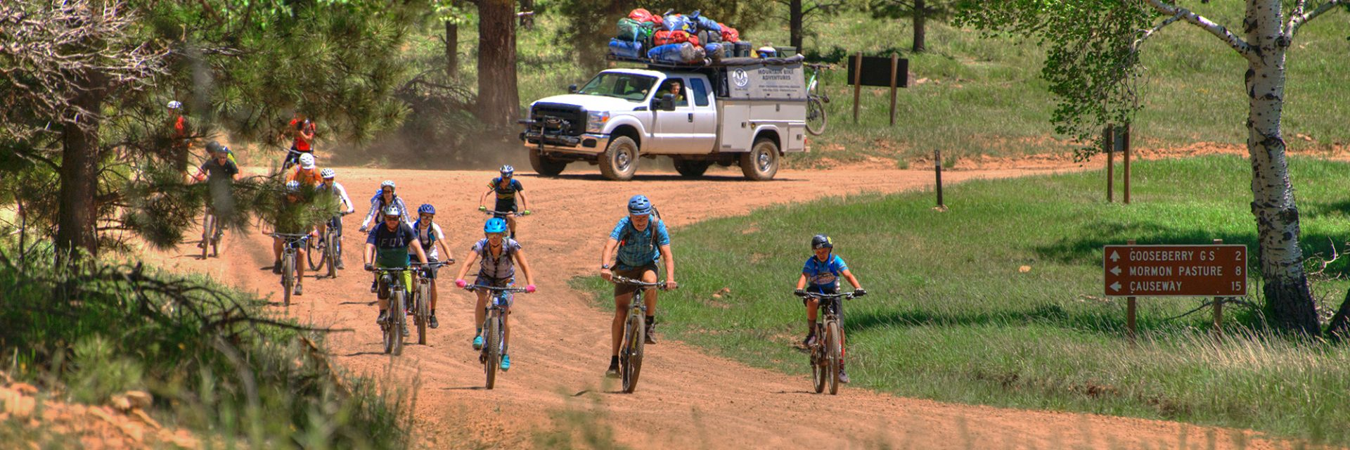 Bears Ears riders follow their guide past an intersection with the support truck behind them