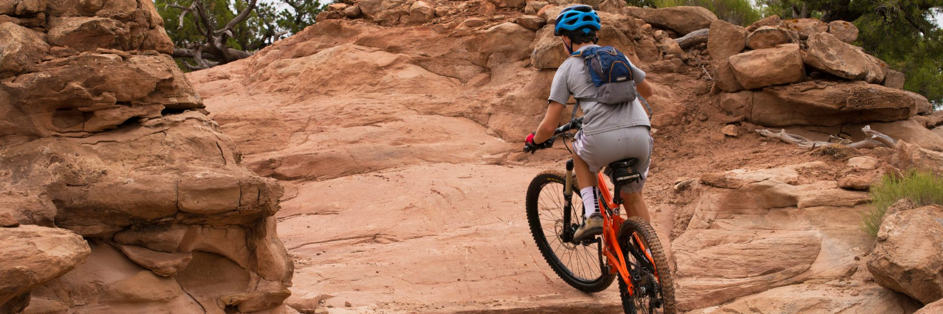 Young rider climbs the steepest section of the Intrepid Trail, Dead Horse Point State Park, Moab UT