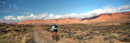 The morning sun lights up The Orange Cliffs in The Maze of Canyonlands NP during Day 3 of a 5-day guided mountain bike adventure