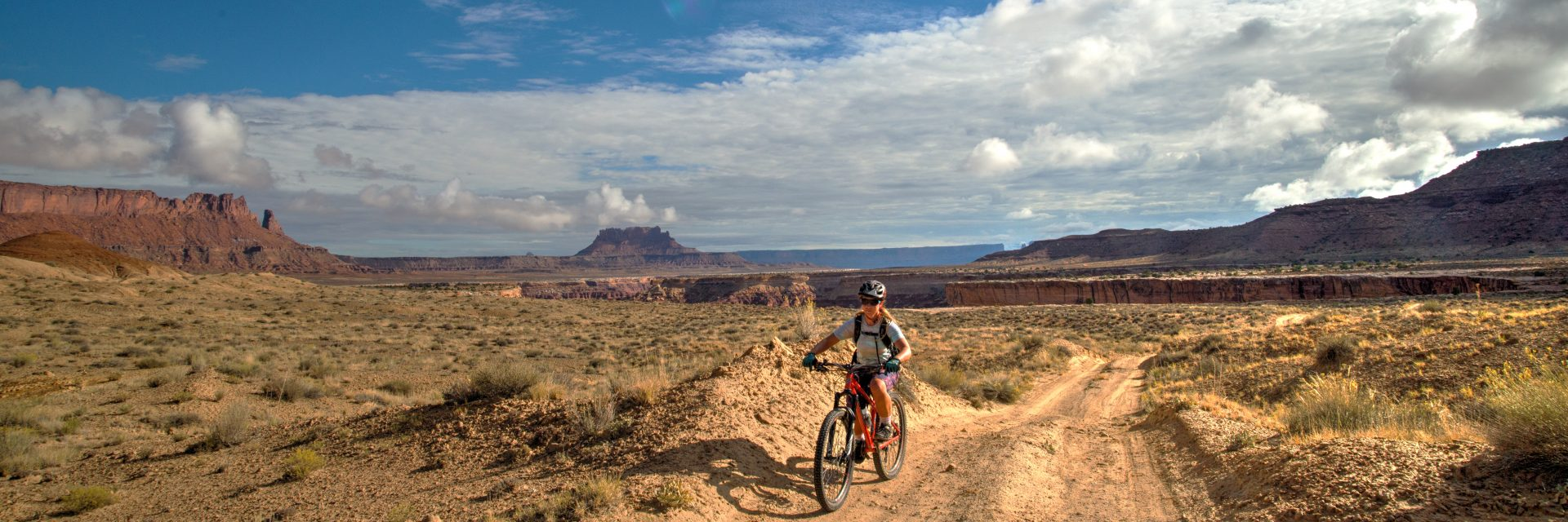 A rider heads away from the edge of The White Rim layer on Day 3 of a 5-day guided mountain bike tour of The Maze in Cayonlands National Park