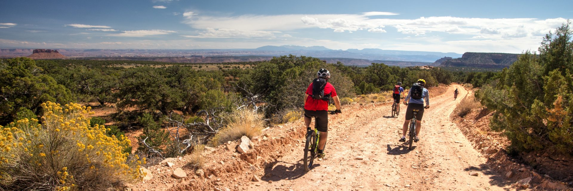 Riders head toward Flint Seep with views of Elk Ridge and The Abajo Mountains in the distance during day one of a 5-day guided mountain bike tour of The Maze, Canyonlands NP