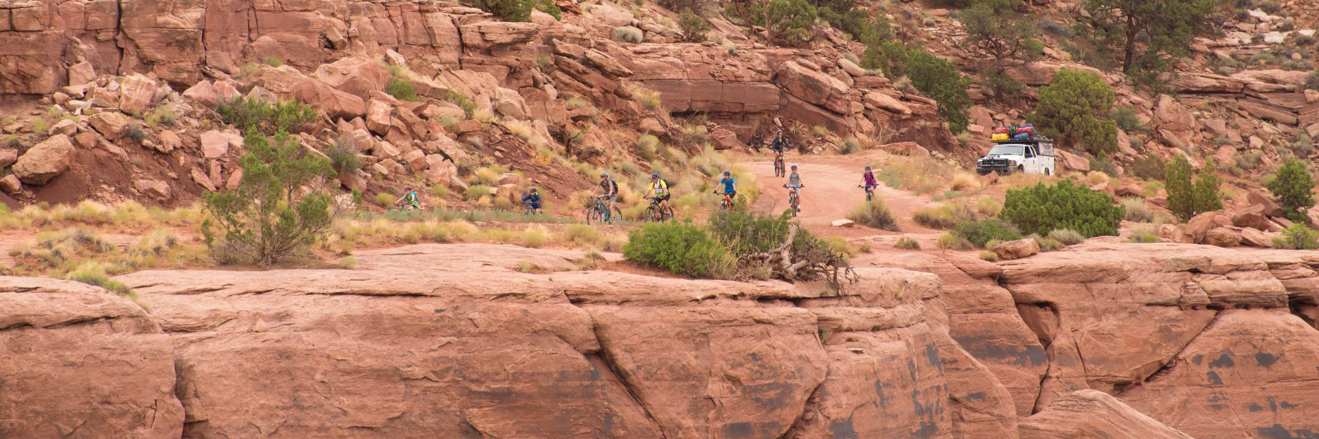 Group mountain biking along the top of The Shafer Trail, White Rim and Canyonlands Full Day guided tour