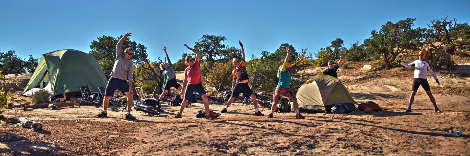 A guide leads riders in yoga stretches each morning prior to the day's ride - Teapot Rock Campground, Canyonlands National Park