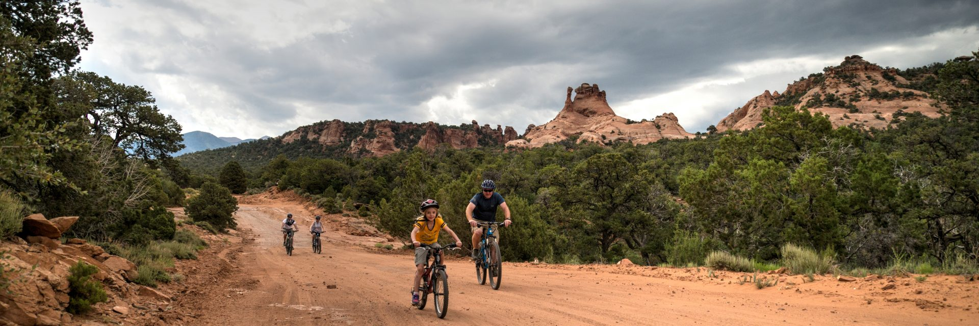 A girl rolls through a rough section of Sand Flats Road as her father looks on while enjoying the Sunrise Downhill guided mountain bike tour
