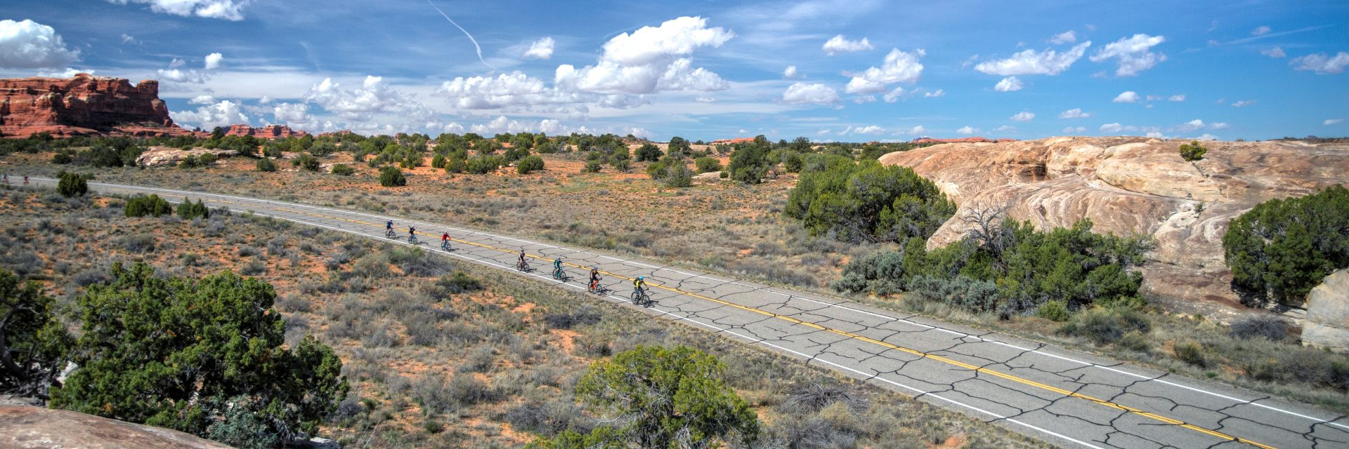 A group of mountain bikers ride a short section of paved road on the way to the Needles Visitor Center during Day 1 of The Needles to Moab guided tour