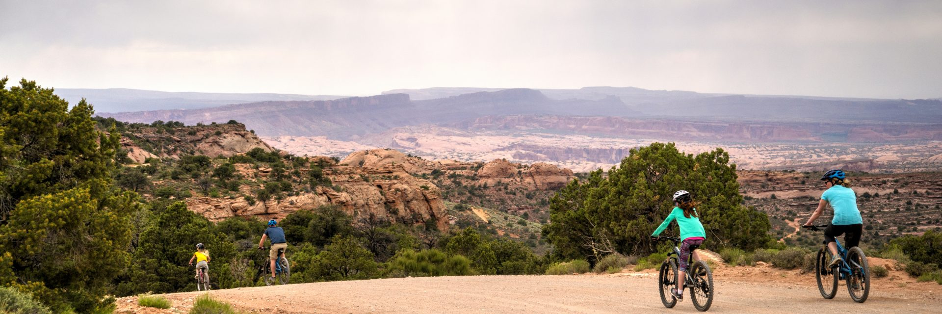 A family coasts down the middle section of the Sand Flats Road on the Sunrise Downhill guided tour with Arches National Park in the distance