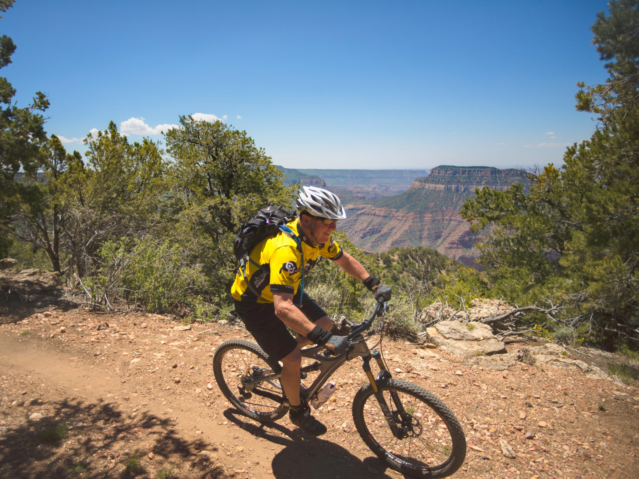 A mountain biker arrives at Fence Point on the Rainbow Rim singletrack on day 3 of the North Rim of the Grand Canyon guided tour