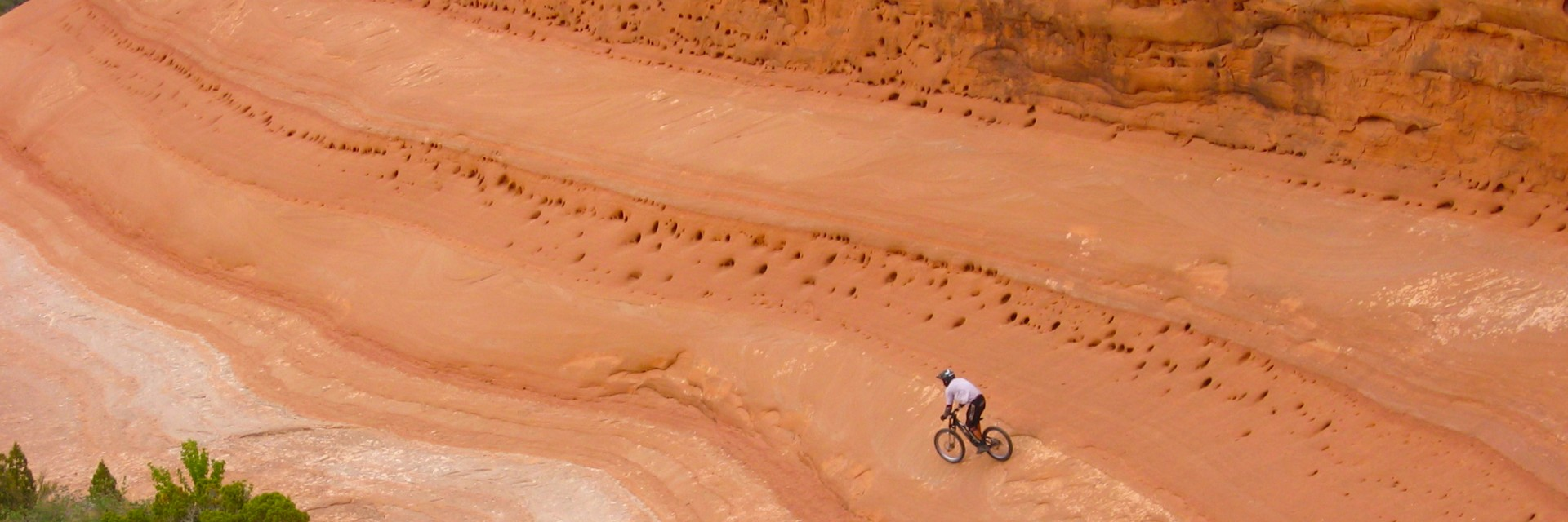 A mountain bike rider descends a massive wall of smooth slickrock during a Bartlett Wash guided mountain bike tour