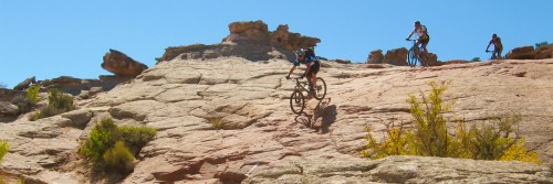 A guide leads mountain bike riders down a steep slickrock section on the Bartlett Wash play area north of Moab UT