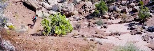 A mountain bike rider leaves a boulder garden on the Klonzo singletrack guided mountain bike tour north of Moab, UT