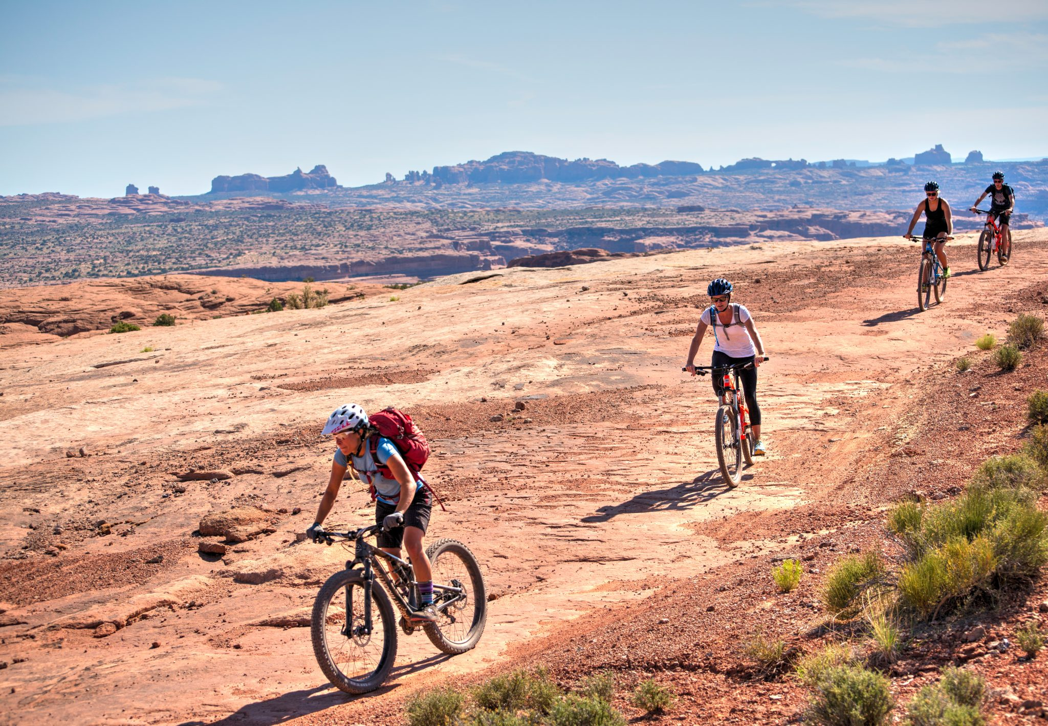 Mountain bike riders follow their guide down a stretch of slickrock on Courthouse Loop with the North Windows section of Arches NP in the background