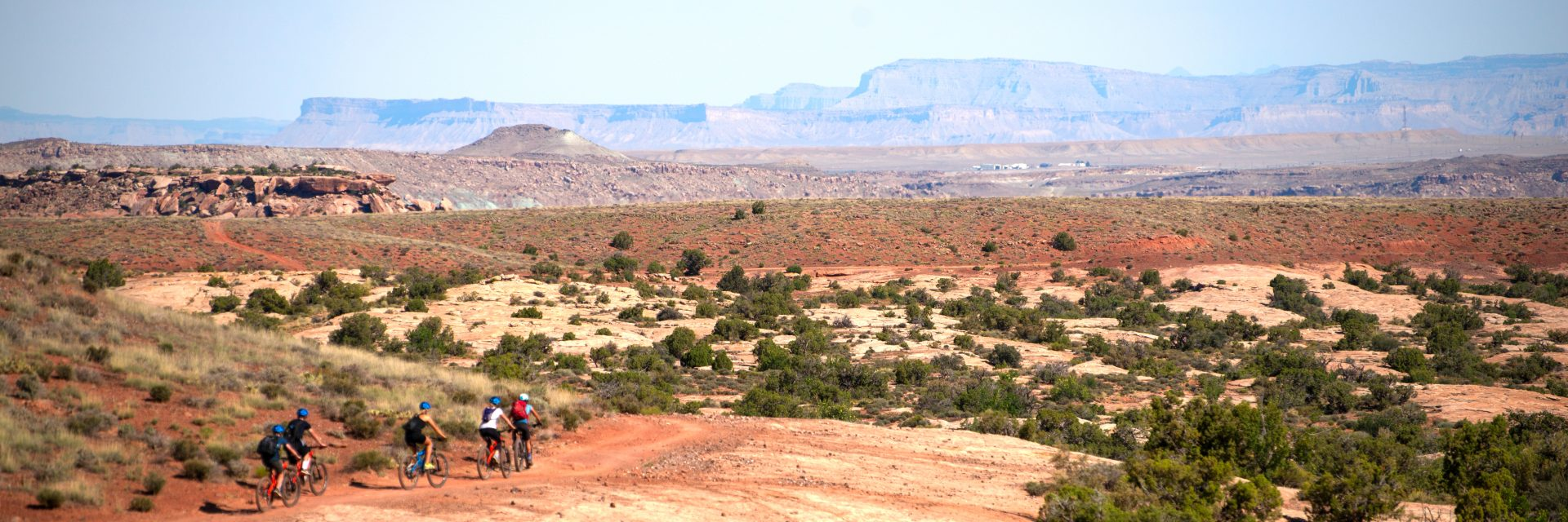 A group of mountain bikers follow their guide around the backside of Courthouse Loop with the Book Cliffs in the distance