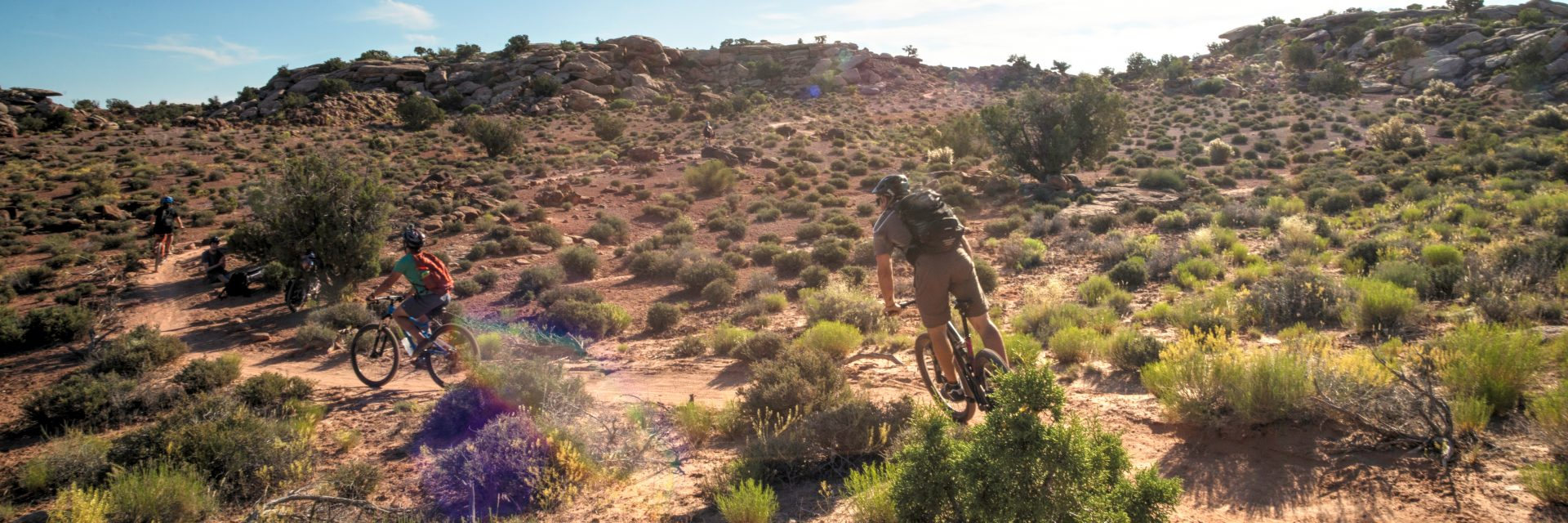 A guide follows a young rider on a singletrack section of the Courthouse Loop Trail guided mountain bike tour in Moab UT