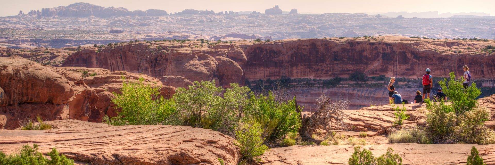 A group of mountain bike riders stop to take in the views of Arches National Park's North Windows section