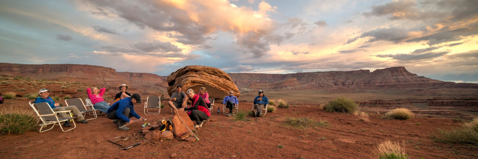 Mountain bikers enjoy an evening campfire above Lockhart Basin at the end of a day's ride on The Needles to Moab guided tour