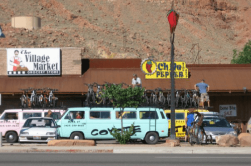 A shuttle van loads bikes in front of Chile Pepper Bike Shop