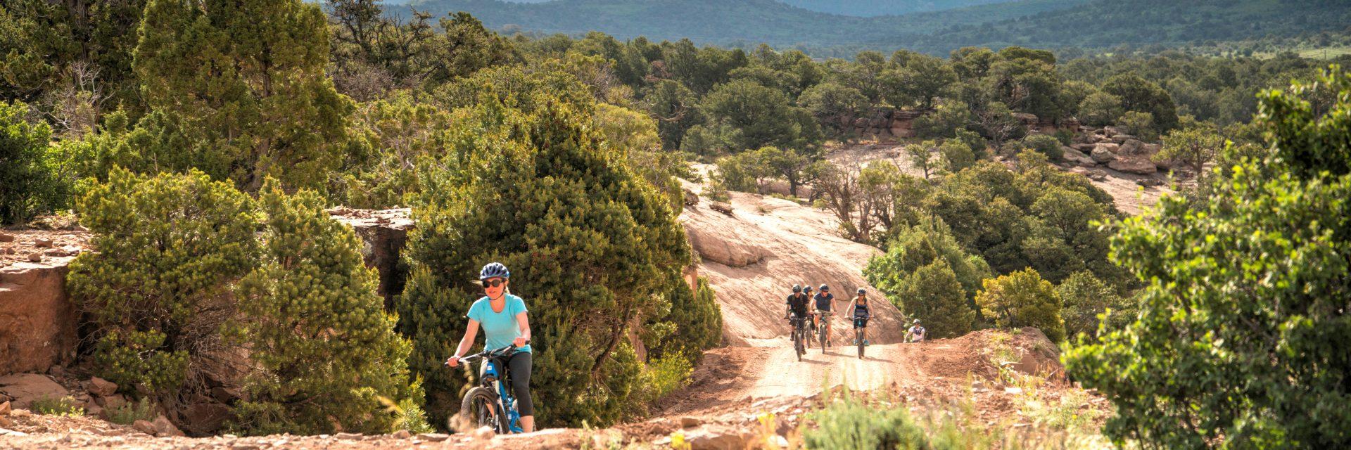 Mountain bike riders follow guide on climb out of Cougar Canyon, Sunrise Downhill guided mountain bike tour, Moab UT