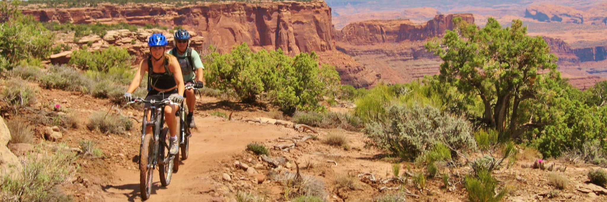 Riders follow a guide on the cliffside section of the Dead Horse Point Singletrack, also known as The Intrepid Trail outside Moab UT