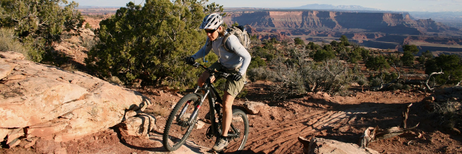 A rider negotiates a slight ledge on Dead Horse Point Singletrack aka Intrepid Trail moderate to intermediate guided mountain bike tour Moab UT