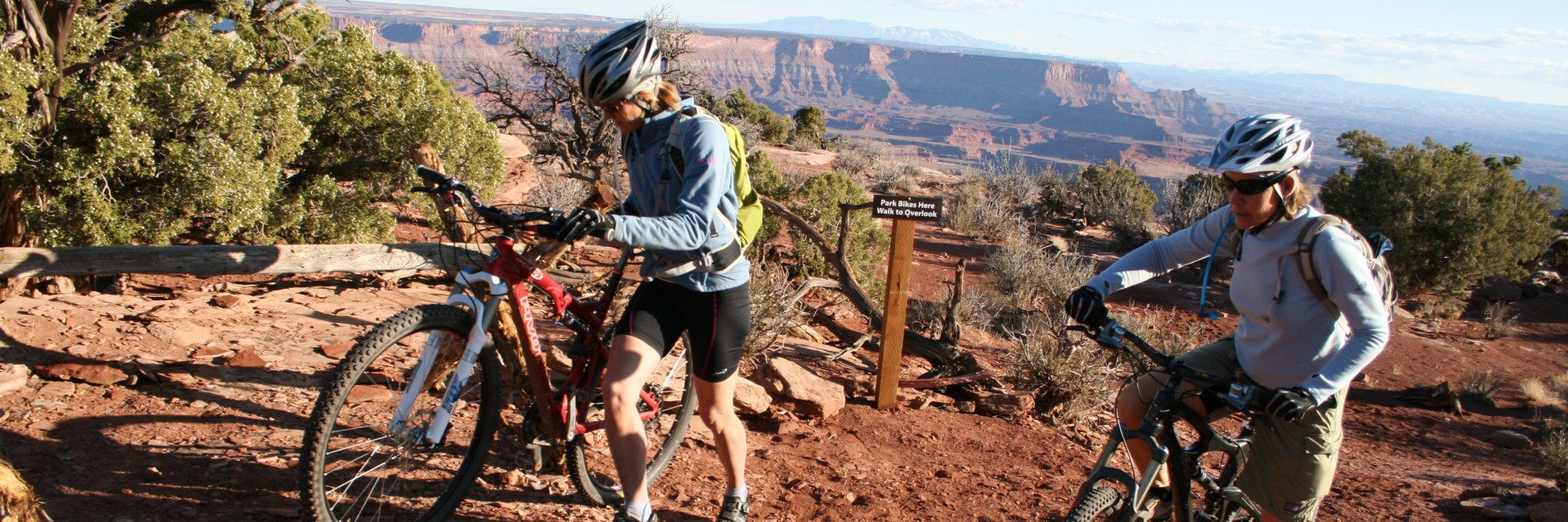 Walking bikes over a tricky section of the Dead Horse Point Singletrack guided mountain bike tour west of Moab UT