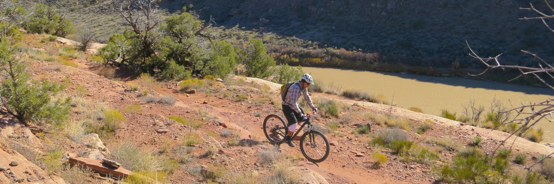 Mountain bike rider traverses a bench above the Colorado River on singletrack just outside Fruita, CO