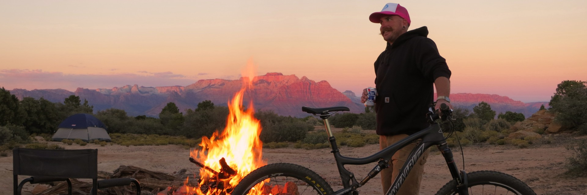 A guide enjoys a bonfire at sunset on a 4-day guided mountain bike tour of Gooseberry Mesa