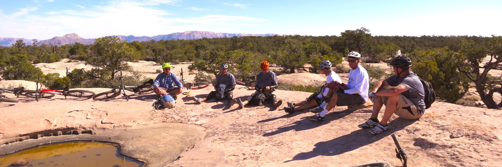 A guide explains the geology of Gooseberry Mesa during a rest stop on a guided mountain bike tour in southwestern Utah