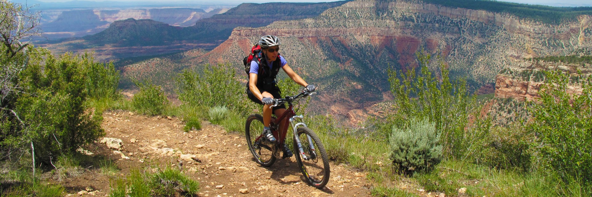 A mountain biker departs Fence Point on the Rainbow Rim Trail during a 5-day guided tour along the North Rim of the Grand Canyon