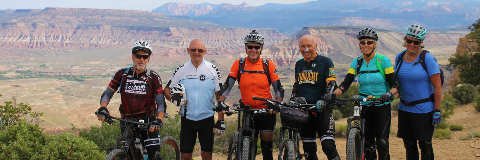 Happy mountain bikers pose on the Rainbow Rim Trail during their guided tour along the North Rim of the Grand Canyon