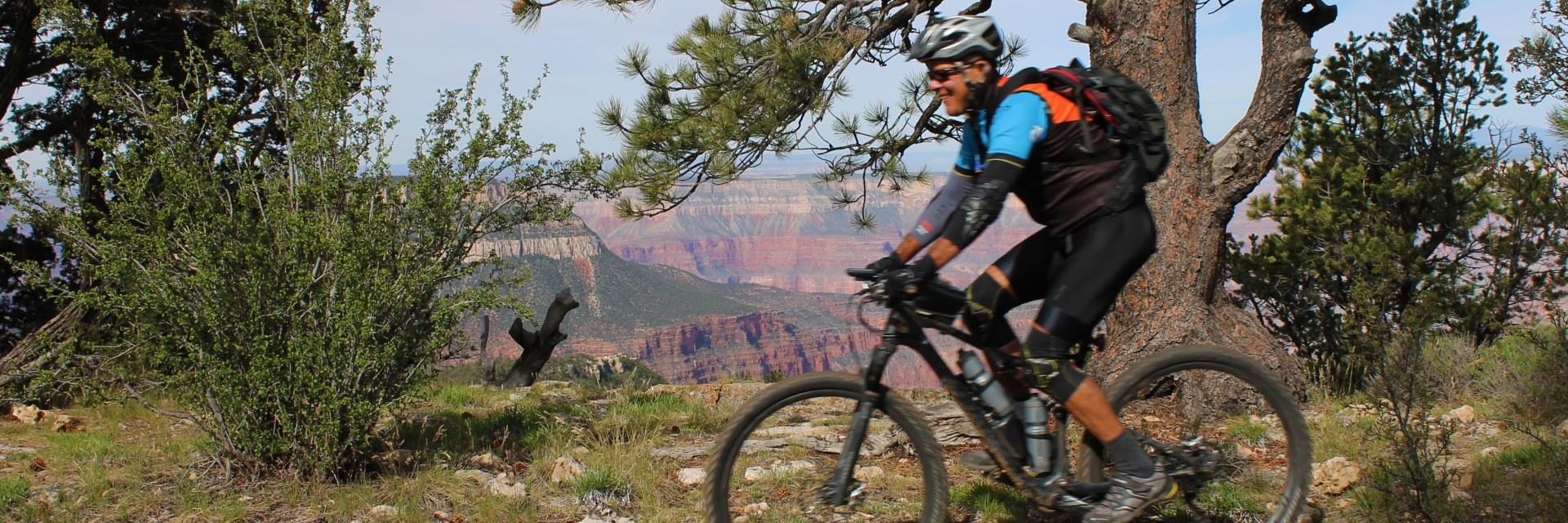 A mountain biker returns to camp at Locust Point on the Rainbow Rim Trail during a 5-day guided tour along the North Rim of the Grand Canyon