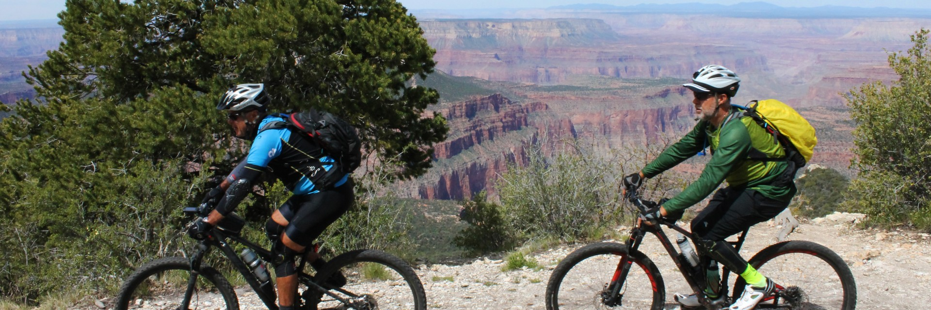 Two riders approach camp at Locust Point on the Rainbow Rim Trail on a four-day guided mountain bike tour