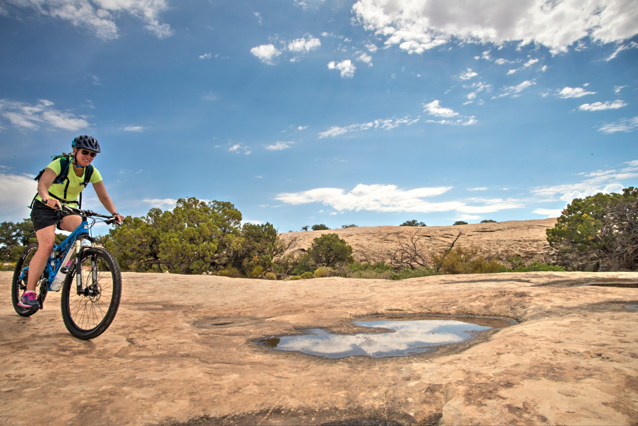 Potholes filled by a recent rain reflect the sunny skies as a rider descends the slickrock section of Klondike Bluff Trail