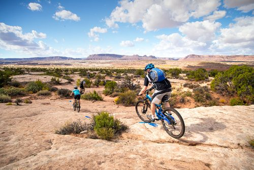 Riders drop down a slickrock section of the Houdini Trail in the Klonzo Area during a half-day guided mountain bike tour north of Moab, UT