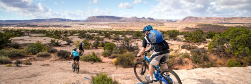 Riders head down a slickrock section of the Houdini Trail during a guided mountain bike tour of the Klonzo Area, with the cliffs of Moab in the background
