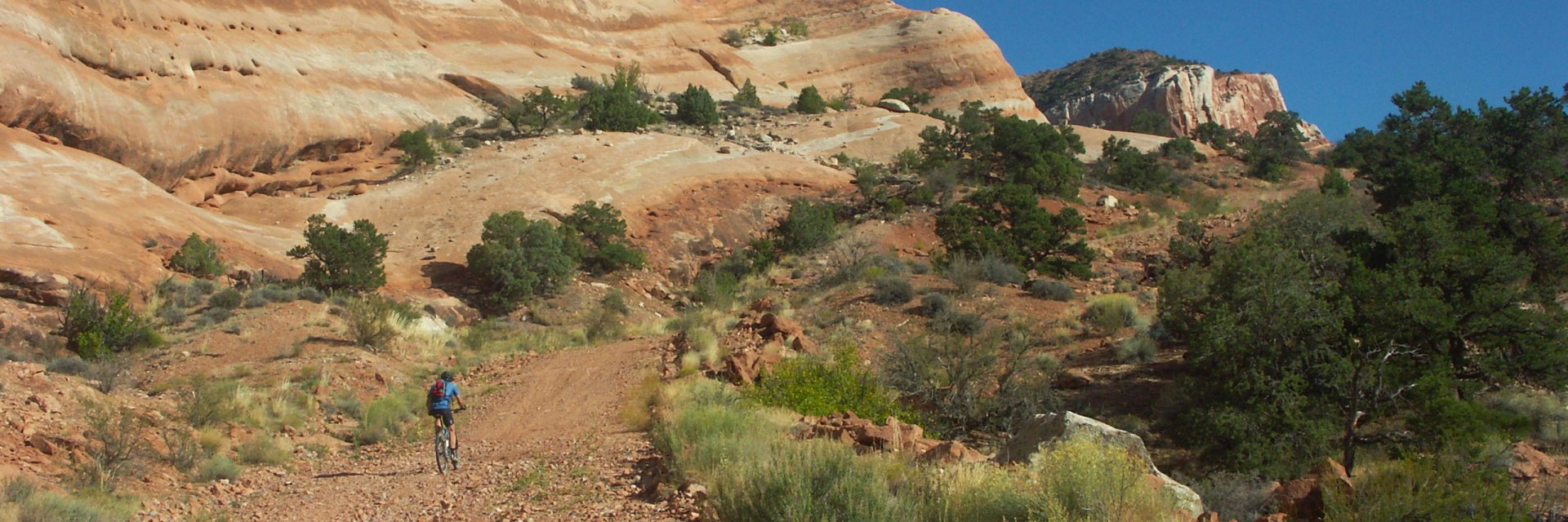 A lone rider climbs the Kokopelli Trail 5-day guided mountain bike tour from Loma CO to Moab UT