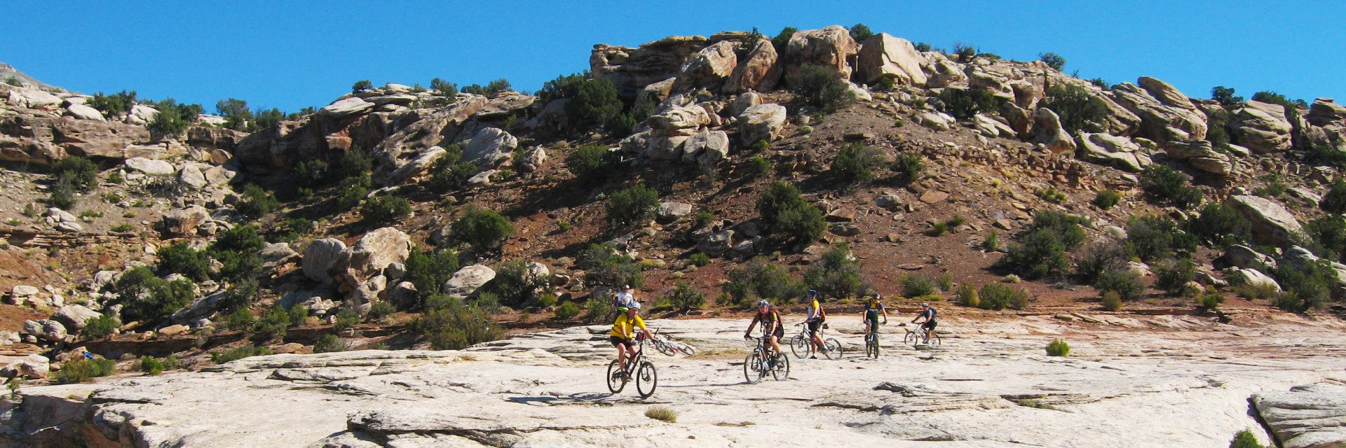 "Riders enjoy a little ""freeriding"" on a slickrock section of the Kokopelli Trail 5-day guided mountain bike tour"