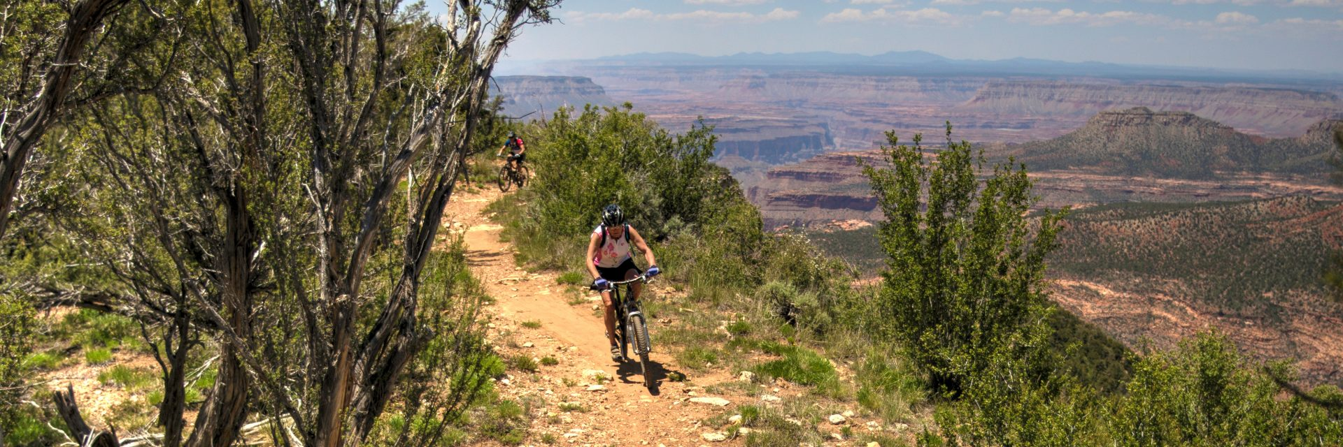 Riders departing Fence Point on the Rainbow Rim Trail during a guided mountain bike tour of the North Rim of the Grand Canyon