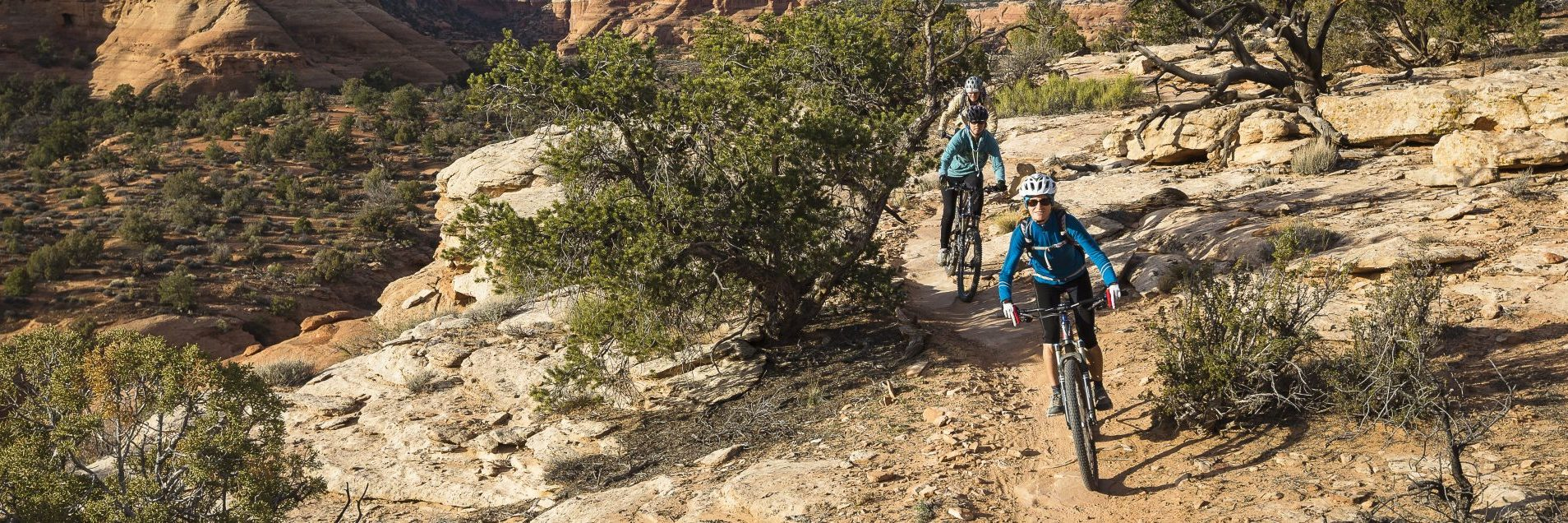 Riders follow a guide on the technical singletrack above Bull Canyon - part of the Magnificent 7 half or full day guided mountain bike tour near Moab UT