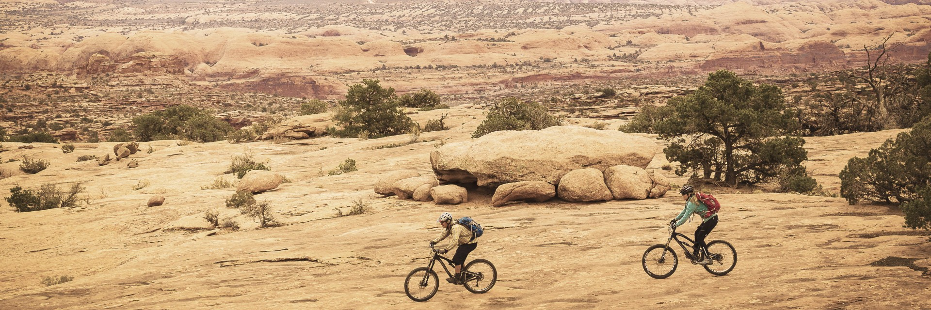 Two mountain bikers roll the slickrock section of the Magnificent 7 Trail west of Moab UT during a guided tour