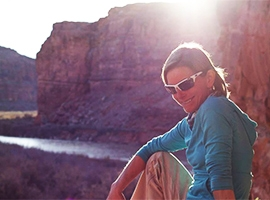 Day Tour Guide Marla Bailey relaxes by the Colorado River near Moab UT